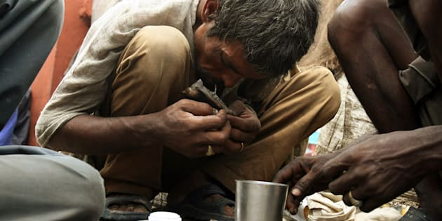 """A drug addict smokes """"smack"""" (low quality heroin) on the street in the old quarters of Delhi."""