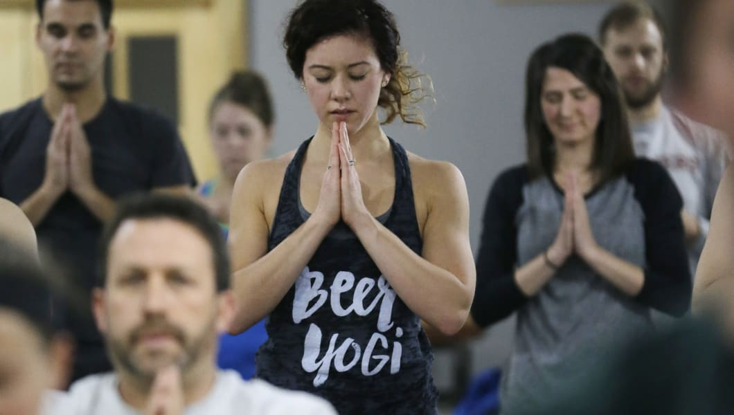 In this Thursday, Dec. 3, 2015, photo, Lauren Kaluza, center, practices yoga at the Platform Beer Co., in Cleveland. Craft breweries are partnering up with yoga studios around the country as more breweries are hosting classes to attract a new crowd to the bars and yoga studios are using the beer to get more men to try yoga. (AP Photo/Tony Dejak)