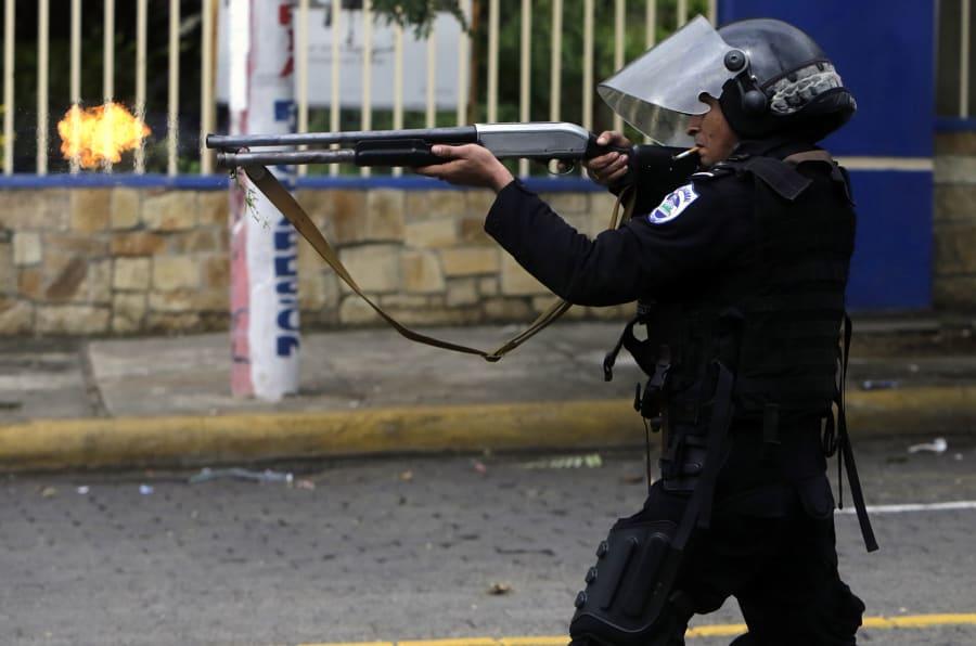 Un policía antidisturbios dispara un arma durante enfrentamientos con estudiantes que participan en una protesta en Managua, el 28 de mayo de 2018.