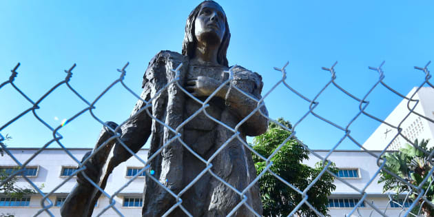 A statue of Christopher Columbus at a downtown Los Angeles park is surrounded by a chain-link fence on October 9, 2017 in Los Angeles, California.