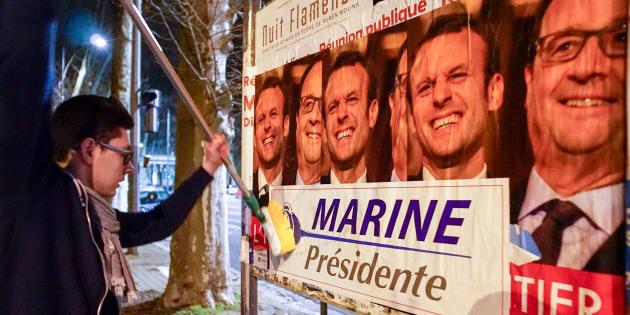 """Des jeunes membres du Front National collent des affiches de campagne de Marine Le Pen sur des affiches où figurent Emmanuel Macron et François Hollande avec pour légende """"L'héritier"""", le 2 février 2017."""