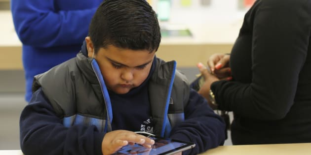 A child uses an iPad Air tablet at the Apple store in San Francisco, California November 1, 2013.