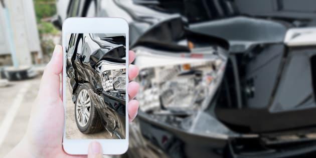 Un ajustador de seguros toma una foto de un vehículo accidentado.