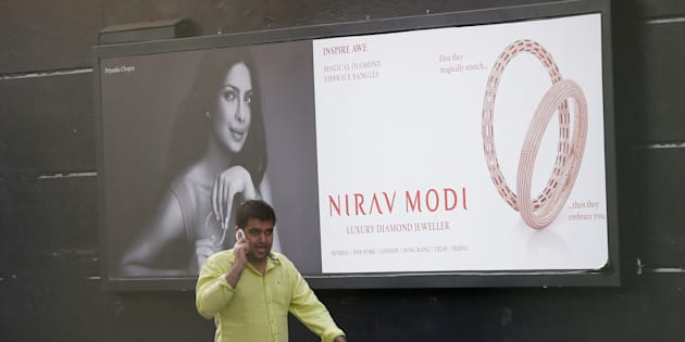 A man talks on a phone as he walks past a Nirav Modi showroom during a raid by the Enforcement Directorate, a government agency that fights financial crime, in New Delhi, India, February 15, 2018. REUTERS/Adnan Abidi