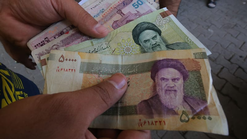 an-iraqi-peddler-holds-in-his-hand-banknotes-of-iranian-rials-for-in-picture-id1013769156