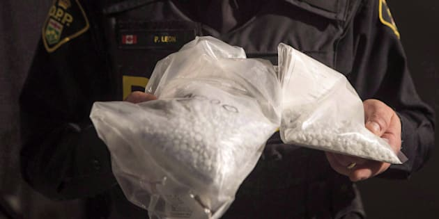 An OPP officer displays bags containing fentanyl as Ontario Provincial Police host a news conference in Vaughan, Ont., on Feb. 23, 2017.