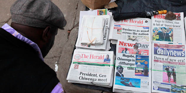 A man reads the headlines of newspapers for sale on a street in Harare, Zimbabwe, November 17, 2017.
