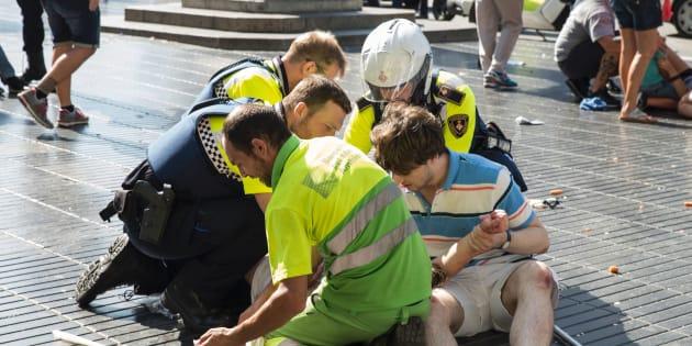 Un grupo de ciudadanos y agentes atiende a una persona herida en el atentado de Barcelona, en La Rambla, el 17 de agosto de 2017.