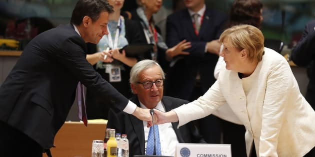 German Chancellor Angela Merkel, right, shakes hands with Italian Prime Minister Giuseppe Conte, left, during a round table meeting at an EU summit in Brussels, Thursday, Oct. 18, 2018. EU leaders meet for a second day on Thursday to discuss migration, cybersecurity and to try and move ahead on stalled Brexit talks. (AP Photo/Alastair Grant)