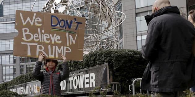 A boy stands with a sign protesting against U.S. Republican presidential candidate Donald Trump, outside the Trump International Hotel and Tower in midtown Manhattan in New York, March 19, 2016.