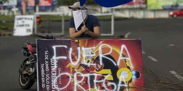 Un joven levanta la bandera de Nicaragua durante una protesta de apoyo a la ciudad de Masaya.