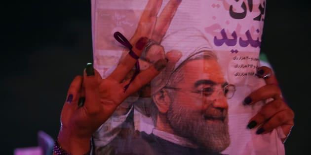 Un partisan du président iranien Hassan Rouhani tient son affiche en célébrant sa victoire lors des élections présidentielles, à Téhéran, en Iran, le 20 mai 2017.