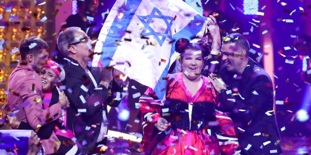 Netta Barzilai, con la bandera israelí de fondo, celebrando su victoria en Eurovisión 2018.