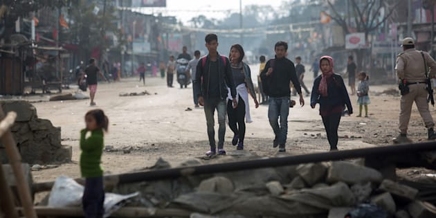 Indian pedestrians walk past temporary roadblocks on the outskirts of Imphal on December 20, 2016, during an ongoing economic blockade led by Naga militant groups in the north-eastern Indian state of Manipur.
