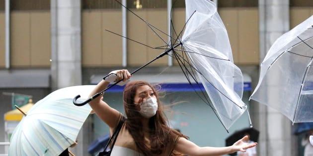Una japonesa pelea contra los fuertes vientos de Shanshan, que le han roto su paraguas.