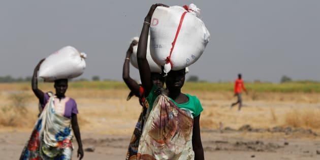Des portent des sacs de nourriture à Nimini, au nord du Soudan du Sud ravagé par la guerre et la famine, le 8 février 2017