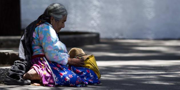 Una mujer de la tercera edad solicita unas monedas a la sombra de un árbol para protegerse del radiante sol de la tarde. Esto a la salida el centro comercial Plaza Universidad, en la colonia Del Valle, Ciudad de México, el 31 de mayo de 2018.