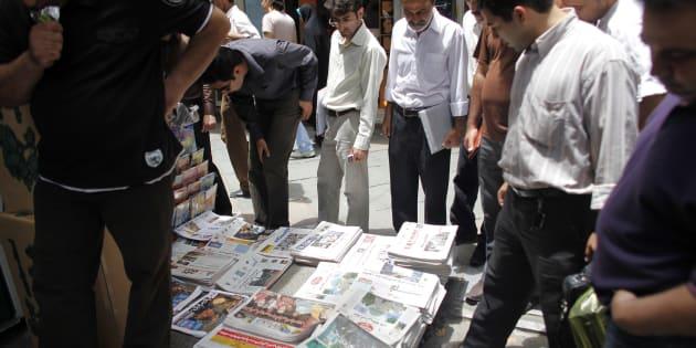 Des Iraniens lisent les journaux d'un kiosque d'une rue de Téhéran, Iran.