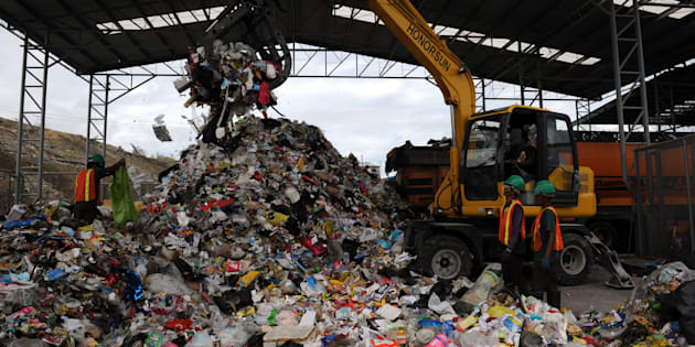 Workers segregate garbage at the Material Recovery Facility near Manila on Feb. 21, 2013. The sorted recyclable materials are sifted by machine shredder which are then compacted, and wrapped with plastic and convert them into bales, where they are bought by companies to be used as alternative burning fuel.
