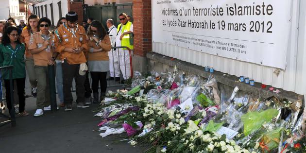 Des fleurs sont déposées devant les portraits des victimes juives de Mohamed Merah, devant l'école Ozar Hatorah de Toulouse, le 25 mars 2012.