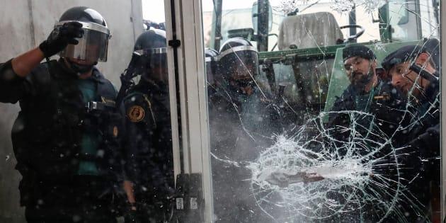 Policías y guardias civiles rompen una puerta de cristal para entrar en un colegio electoral el 1 de octubre.
