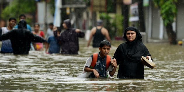 An Indian woman wades with her son through flooded street during heavy rain showers in Mumbai.