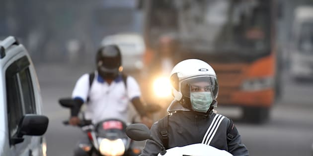 A motorcyclist wearing a face mask drives along a road in New Delhi.