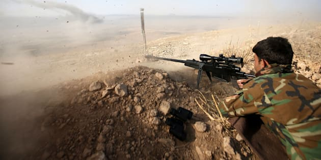A Kurdish peshmerga fighter shoots during an operation to attack Islamic State militants in the town of Naweran, near Mosul, October 23, 2016.