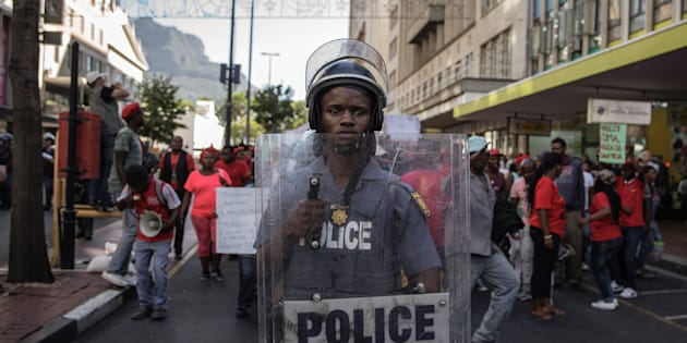 A South African riot policeman stands by as South African opposition party Economic Freedom Fighters (EFF) members and supporters sing and dance while shouting slogans against the South African president ahead of the annual State Of The Nation Address (SONA) on February 9, 2017 in Cape Town.