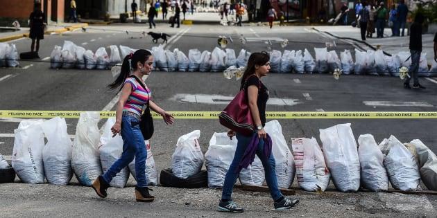 Des femmes traversent une rue bloquée par des manifestants anti-Maduro à Caracas, le 26 juillet.