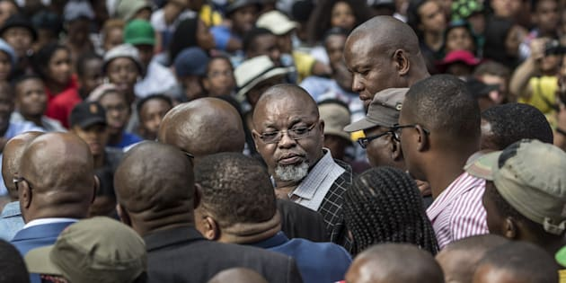 Secretary General of the African National Congress ruling party (ANC) Gwede Mantashe (C) looks back among the crowd outside the Luthuli House, the ANC headquarters.