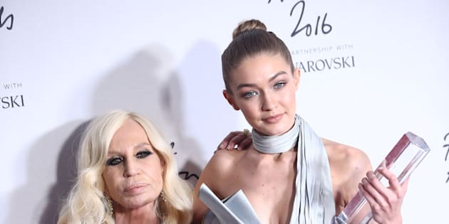 Gigi Hadid, winner of the International Model award (R) and designer Donatello Versace pose for photographers at the Fashion Awards 2016 in London, Britain December 5, 2016. REUTERS/Neil Hall