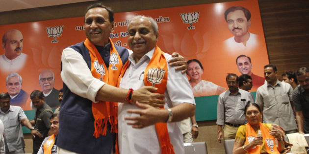 Vijay Rupani, left, state president of Bharatiya Janata Party (BJP) in Gujarat, is congratulated by Nitin Patel as he is selected as Chief Minister of the state in Gandhinagar, India, Friday, Aug. 5, 2016. Patel will take over as Deputy Chief Minister. (AP Photo/Ajit Solanki)