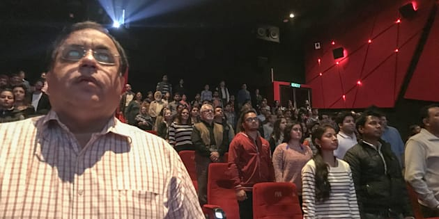 Audience members stand for the Indian national anthem before a movie starts at a cinema in New Delhi.