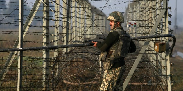 An Indian Border Security Force  soldier patrols near the fenced border with Pakistan in Suchetgarh, southwest of Jammu.
