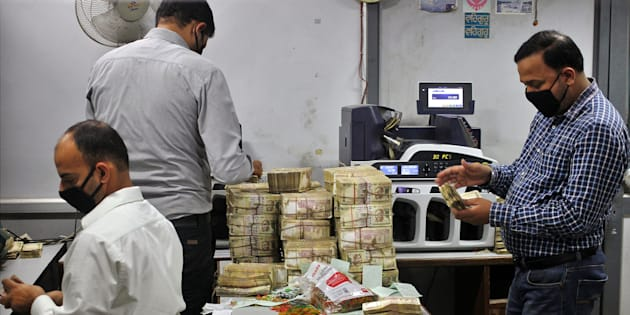 Bank employees count old ₹500 banknotes inside a bank.