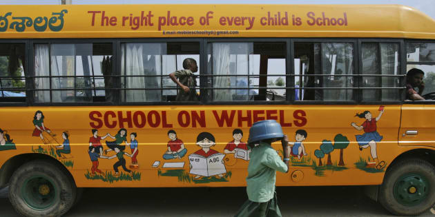 """Bhavani, 8, covers her head with a plastic container as she walks past a bus which has been converted into a school called """"School on Wheels"""", at a slum area in Hyderabad November 1, 2011."""
