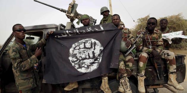 Des soldats nigérians tiennent un drapeau de l'organisation terroriste Boko Haram.