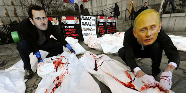 Actors  from Avaaz wearing giant masks of Bashar al-Assad and Vladimir Putin dump dozens of bloodied body bags outside the UN Security Council building January 24,2012  as members of the UN Security Council meet in New York to discuss the Syria crisis, Avaaz will deliver a petition signed by more than 620,000 people worldwide calling for the UN to refer President Bashar al-Assad to the ICC for crimes against humanity.  AFP PHOTO / TIMOTHY A. CLARY (Photo credit should read TIMOTHY A. CLARY/AFP/Getty Images)