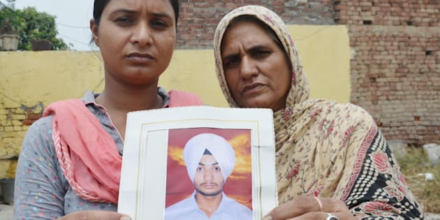 Bhoewal Village residents Gurpinder Kaur (L), along with her mother, hold a photo of her brother Manjinder Singh, who was reportedly abducted in Mosul, Iraq, on June 18, 2014. (Photo by Sameer Sehgal/Hindustan Times via Getty Images)