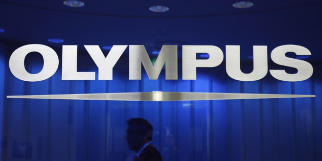 A man walks behind a logo of Japan's Olympus Corp at the company headquarters in Tokyo April 3, 2012. Japan's Olympus Corp may be able to recover from a $1.7 billion accounting fraud without raising capital, despite interest in an equity alliance from several investors including electronics giant Sony, Hiroyuki Sasa, its nominee president said on Tuesday.  REUTERS/Yuriko Nakao (JAPAN - Tags: BUSINESS LOGO)