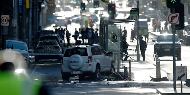 The white car involved in the crash, as police and emergency personnel work at the scene in Flinders Street in Melbourne