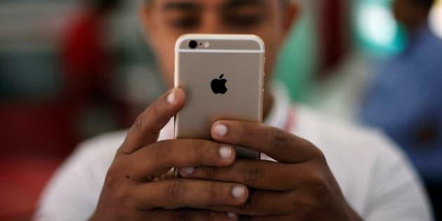 A salesman checks a customer's iPhone at a mobile phone store in New Delhi, India, July 27, 2016. REUTERS/Adnan Abidi