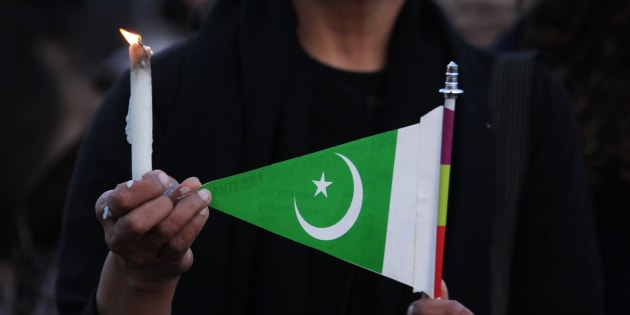 A woman holds a candle and a Pakistani flag as she takes part in a protest against terrorism in Islamabad March 17, 2015. Suicide bombings outside two churches in Lahore killed 14 people and wounded nearly 80 others during services on Sunday in attacks claimed by a faction of the Pakistani Taliban.  REUTERS/Faisal Mahmood