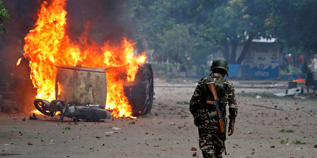 A member of the security forces walks towards a burning vehicles during violence in Panchkula, India, August 25, 2017. REUTERS/Cathal McNaughton     TPX IMAGES OF THE DAY