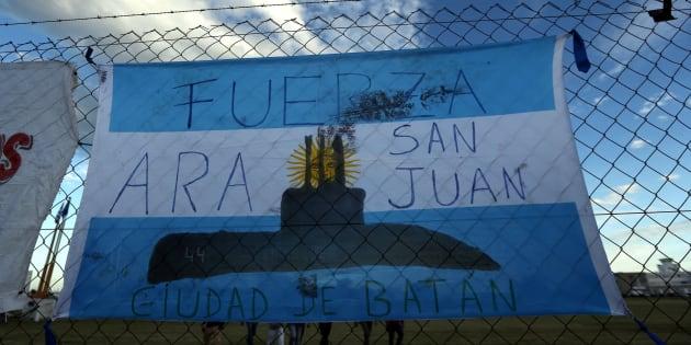La gente camina detrás de una bandera de Argentina desplegada en una valla, en apoyo de los 44 miembros de la tripulación del submarino ARA San Juan.