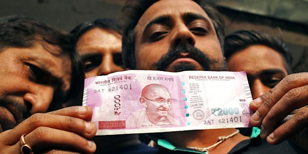 A man displays a new 2000 Indian rupee banknote after withdrawing from a bank.