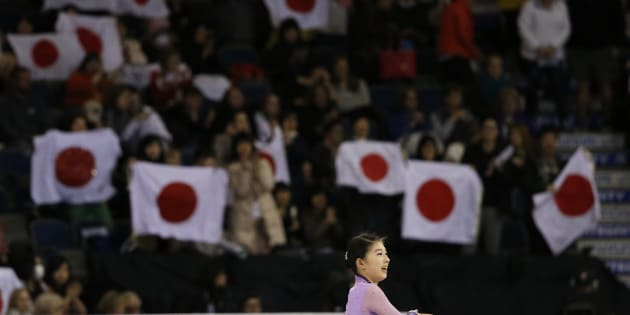 Fans wave Japanese flags as Yuka Nagai of Japan finishes her performance during the Ladies Short program at Skate Canada International in Lethbridge, Alberta October 30, 2015. Fifty-six Olympic and world championship athletes are competing in the event, which is the second of six stops on the International Skating Union (ISU) Grand Prix of Figure Skating Series. REUTERS/Jim Young