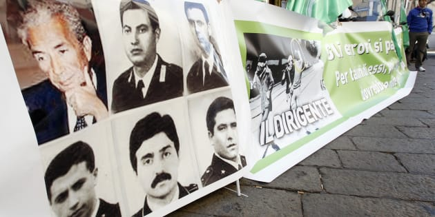 A banner with pictures of the 39th prime minister of Italy Aldo Moro (top L), and members of his escort killed by Red Brigades, is pictured in Milan March 29, 2012. A set of documents from Italy's Red Brigades terrorist group went under the hammer on Thursday for 17,000 euros in an auction that reopened old wounds and angered some victims of the violence which plagued Italy in the 1970s and 1980s. REUTERS/Alessandro Garofalo (ITALY - Tags: CRIME LAW POLITICS ENTERTAINMENT SOCIETY)