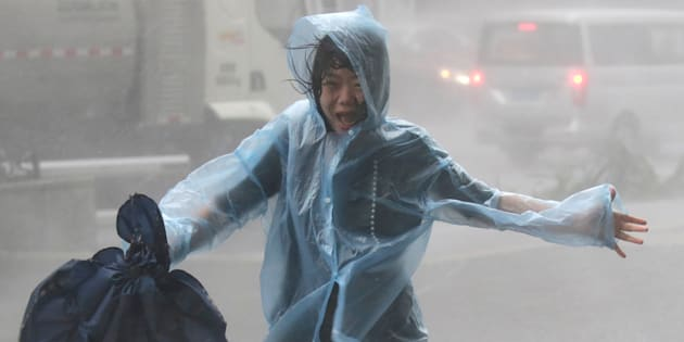 A woman runs in the rainstorm as Typhoon Mangkhut approaches in Shenzhen China on Sunday Sept. 16 2018